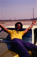 Student Poses for Picture on Car