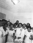 Group of women in white gowns and conference ribbons standing next to punch table