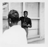 Mississippi State Sovereignty Commission photograph of an African American male holding a walkie-talkie and an African American woman standing in front of a county government office during a demonstration for welfare rights, Jackson, Mississippi, 1960s