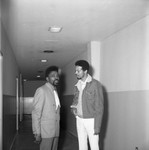 Roland Bynum and an unidentified man talking in a hallway, Los Angeles, 1969