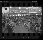 Jesse Jackson speaking to a large crowd and reporters at McKinley Baptist Church in South Central Los Angeles, Calif., 1984