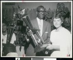 African American man holding golfing trophy, Los Angeles, 1958