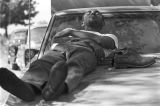 """Man asleep on the hood of a car at a rest stop during the """"March Against Fear"""" begun by James Meredith."""