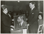 Mrs. Ira T. Lewis, wife of the president of the Pittsburgh Courier Publishing Company, presents a photograph of the late Robert L. Vann, former publisher of the Pittsburgh Courier, to a representative of the shipyard workers at the launching of the Liberty ship SS Robert L. Vann