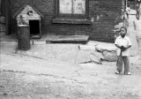 Jasper Wood Collection: Boy standing near dog house