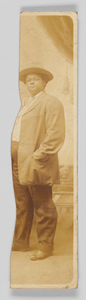 Piece of a photographic postcard of an unidentified woman in a jacket and pants