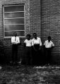 Stokely Carmichael and others, standing against the wall of a brick church building in Prattville, Alabama, during a meeting of the Autauga County Improvement Association.