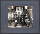 11 men seated on steps