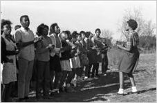 Lula Williams, an SCLC worker from Montgomery, leading a group of young men and women in singing before a meeting at a small rural church building in Greenville, Alabama.