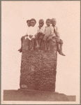 Children sitting on a stone structure, 1902