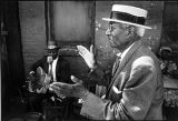 African American man in straw boater hat on Peoria Street, east of Maxwell Street