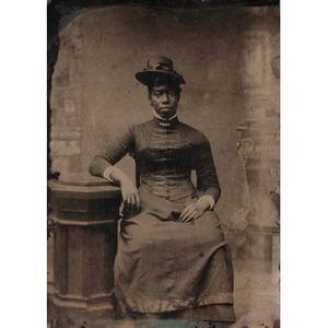 An African-American woman sitting by a pedestal.