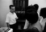 Man explaining scientific equipment to a group of young women from Lee County, Alabama, during a field trip to Auburn University.