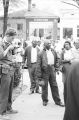 Two men in a crowd in downtown Eutaw, Alabama, standing in front of Perkins Barber Shop and the Eutaw Beauty Salon.