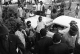 """Martin Luther King, Jr., William M. Branch, Ralph Abernathy, Ben """"Sunshine"""" Owens, and others, greeting a small crowd of people while walking toward a building, probably First Baptist Church in Eutaw, Alabama."""