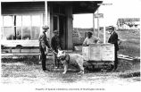 Four men, two of them African American, with dog harnassed to wagon outside store, Eagle, n.d