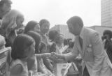"Andrew Young shaking hands with a woman in a crowd in downtown Atlanta, Georgia, during the Democratic National Committee's regional conference, ""Victory '68."""