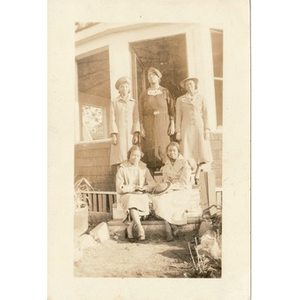 A group of women pose on the steps of an enclosed gazebo.