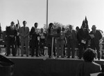 Julian Bond, Diane Watson, Kenneth Hahn and others standing on an outdoor stage, Inglewood, California, 1985