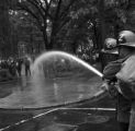 Firemen spraying civil rights demonstrators with a hose at Kelly Ingram Park during the Children's Crusade in downtown Birmingham, Alabama.