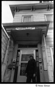 Young African American man on the front steps of 199 Harvard St., Cambridge, Mass.; banner over doorway reads 'Cambridge is a city, not a highway'