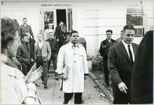 Hamilton Holmes, one of the first two African-American students to integrate the University of Georgia, leaving a campus building in Athens, Georgia, January 1961. White male students are shown in the background.