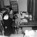 Nun assisting children as they select used clothing and shoes from racks and boxes at Nazareth Catholic Mission in Montgomery, Alabama.