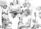 Barbara Howard Flowers and Sandra Colvin, staff members at the Southern Courier, at a meeting of the Autauga Count Improvement Association outside a brick church building in Prattville, Alabama.