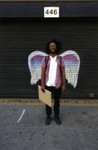 Unidentified man posing in front of a mural depicting angel wings