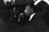 Joseph Lowery and Martin Luther King, Jr., seated behind the speaker during a meeting at St. Paul AME Church in Birmingham, Alabama.