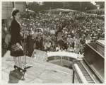 Lena Horne, African American actress, singer, and sponsor of the SS George Washington Carver, standing on stage and addressing a crowd at a war bond rally before the launching of the Liberty ship SS George Washington Carver