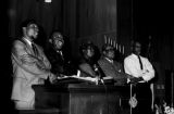 Richard Boone, Ralph Abernathy, and others, linking arms and singing at the podium during a meeting at Holt Street Baptist Church in Montgomery, Alabama.