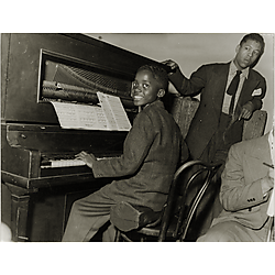 Ahmad Jamal seated on instrument case playing the piano
