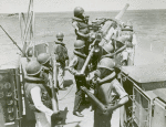 African American seamen delivering shells and loading the anti-aircraft gun aboard a vessel on the Atlantic patrol