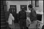 Jesse Fuller speaking with man and woman in front of his home in West Oakland