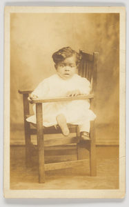 Photographic postcard of an infant in a wooden chair