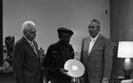 "KPIX general manager Al Constant (left) and former museum director John Peetz presenting Jesse Fuller with film ""Jesse Fuller: Portrait"" during concert at the Oakland Museum"