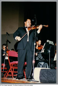 [Low left-angled full shot of a man playing the violin and standing in front of other performers, who are sitting in chairs, on a stage] Christmas/Kwanzaa Concert
