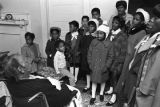 """Children in the group """"Buds of Promise"""" from Mt. Zion AME Zion Church in Montgomery, Alabama, singing to an elderly woman in her home."""