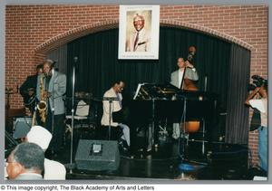 Photograph of a Claude Johnson, Marchel Ivery, and other band members performing on stage Al Lipscomb Tribute