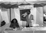 Black Agenda Business Fair participants standing in their booth, Los Angeles, 1983