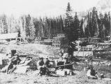 Men cooking and eating while taking a break from their work at the lumber mill seen behind them.