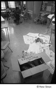 Young boy hiding in a cardboard box in the classroom, Liberation School