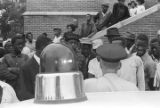 Police officer speaking to a crowd of African Americans looking toward the scene of the 16th Street Baptist Church bombing.