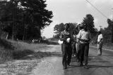 Edward Rudolph leading marchers down an unpaved road in Prattville, Alabama, during a demonstration sponsored by the Autauga County Improvement Association.