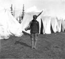 Boy dressed in military uniform with rifle at camp, Fort Lawton, May 1900