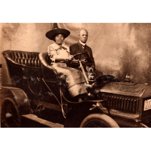 African-American couple posing in a car
