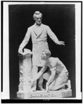 [Sculpture of Abraham Lincoln standing above crouched slave wearing manacles]