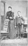 Unidentified standing figures: woman, her folded arms leaning on back of chair, and young man, probably her son, left hand on book