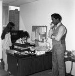 Donald Bohana talking on a phone in an office, Los Angeles, 1976